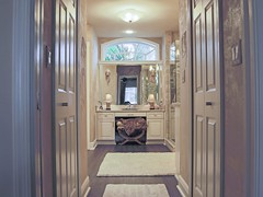 His and Hers Closets Line Entry to Master Suite with Arch Window Above Make-up Station
